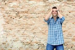 Homem novo no desespero perto da parede de tijolo Imagens de Stock