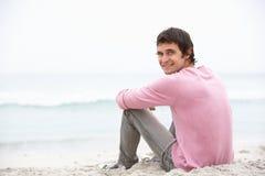 Homem novo no feriado que senta-se na praia do inverno Fotografia de Stock