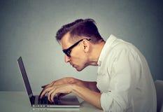 Homem novo no funcionamento de vidros no computador que senta-se na mesa Fotografia de Stock Royalty Free