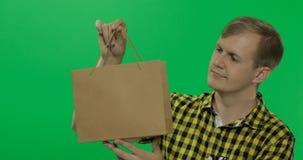 Homem novo no fundo chave do croma verde da tela com saco de compras foto de stock