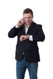 Homem novo no nd do telefone que olha o relógio Fotos de Stock