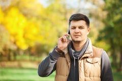 Homem novo no parque que fala no smartphone Fotografia de Stock Royalty Free