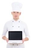 Homem novo no portátil guardando uniforme do cozinheiro chefe com o isola da tela vazia Fotografia de Stock Royalty Free