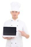 Homem novo no portátil guardando uniforme do cozinheiro chefe com o isola vazio da tela Fotografia de Stock Royalty Free