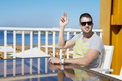 Homem novo no restaurante do mar que chama o garçom foto de stock royalty free