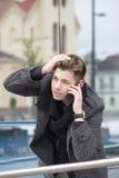 Homem novo no revestimento que mantém um telefone celular disponivel e a fala imagem de stock