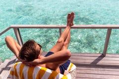 Homem novo no roupa de banho que relaxa em um terra?o e que aprecia a liberdade em um destino tropical imagens de stock