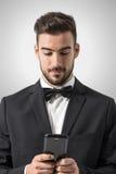 Homem novo no smoking com o laço que guarda a mensagem texting do telefone celular Fotografia de Stock
