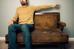 Homem novo no sofá que aponta certo fotografia de stock royalty free