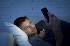 Homem novo no sofá da cama em casa tarde na noite usando o telefone celular na luminosidade reduzida relaxado no conceito da tecn Foto de Stock