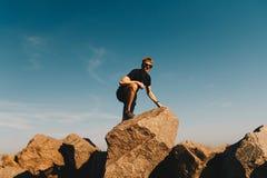 Homem novo no sportswear que corre na fuga de montanha com tempo ensolarado fotos de stock royalty free