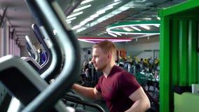 Homem novo no sportswear usando a máquina elíptica e fazendo o cardio- exercício no gym filme