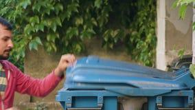 Homem novo no sportswear vermelho que joga afastado desperdícios filme