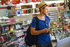 Homem novo no supermercado que escolhe produtos imagens de stock royalty free