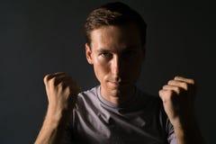 Homem novo no t-shirt em um fundo escuro que guarda os punhos em sua cara foto de stock royalty free