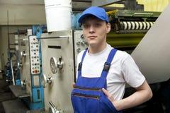 Homem novo no tampão que trabalha na máquina de impressão deslocada Imagens de Stock