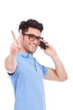 Homem novo no telefone que mostra a paz Fotografia de Stock Royalty Free