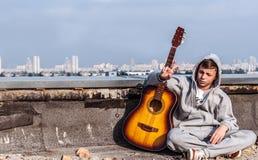 Homem novo no telhado com uma guitarra Fotografia de Stock Royalty Free