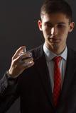 Homem novo no terno que guarda o perfume do homem em sua mão Foto de Stock Royalty Free