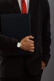 Homem novo no terno que mantém o dobrador disponivel Fotos de Stock Royalty Free