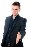 Homem novo no terno que oferece agitar a mão Imagem de Stock Royalty Free