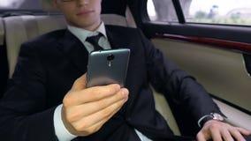 Homem novo no terno usando o smartphone ao sentar-se no banco traseiro do carro, tecnologias video estoque