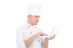 Homem novo no uniforme do cozinheiro chefe com o portátil isolado no branco Fotografia de Stock Royalty Free