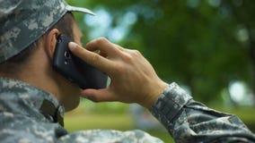 Homem novo no uniforme militar que fala no telefone que senta-se no parque, uma comunicação vídeos de arquivo