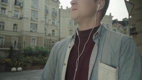 Homem novo nos fones de ouvido que escuta a música com entusiasmo filme