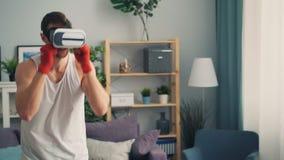 Homem novo nos vidros aumentados modernos da realidade que encaixotam no apartamento que treina apenas video estoque