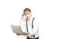 Homem novo nos vidros com o portátil com emoção Fotografia de Stock Royalty Free