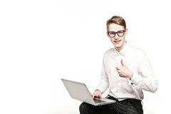 Homem novo nos vidros com o portátil com polegares da emoção acima Imagem de Stock Royalty Free