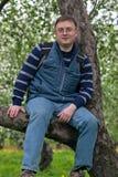 Homem novo nos vidros que sentam-se em uma árvore Imagem de Stock