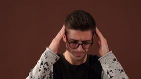 Homem novo nos vidros que tocam em sua cabeça com dor de cabeça forte do sentimento da mão vídeos de arquivo