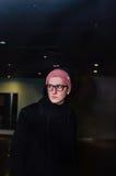 Homem novo ocasional elegante que está no fundo abstrato escuro Imagens de Stock Royalty Free