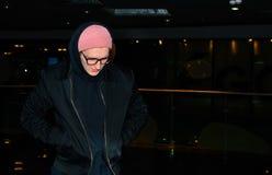 Homem novo ocasional elegante que está no fundo abstrato escuro e que olha para baixo Imagem de Stock Royalty Free