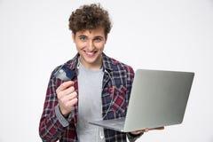 Homem novo ocasional feliz que está com portátil Imagens de Stock Royalty Free