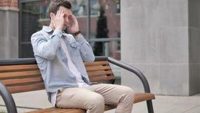 Homem novo ocasional forçado com o assento da dor de cabeça exterior video estoque