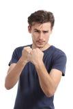 Homem novo ocasional pronto para lutar o ataque com punho acima Fotografia de Stock Royalty Free
