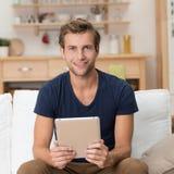 Homem novo ocasional que guarda um tabuleta-PC foto de stock