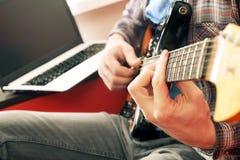Homem novo ocasionalmente vestido com a guitarra que joga músicas na sala em casa Conceito em linha das lições da guitarra Pratic Fotografia de Stock Royalty Free
