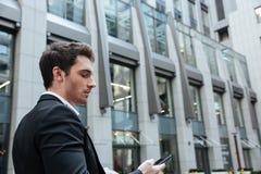 Homem novo ocupado que trabalha com smartphone Foto de Stock