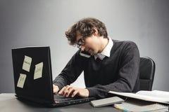 Homem novo ocupado que trabalha em na seu portátil e chamada foto de stock