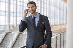 Homem novo otimista no prédio de escritórios brilhante moderno do telefone Fotos de Stock Royalty Free