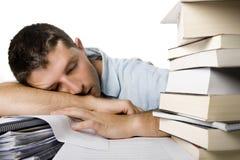 Homem novo Overwhelmed que dorme sobre uma pilha dos livros Fotos de Stock Royalty Free