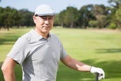 Homem novo pensativo com clube de golfe Fotografia de Stock Royalty Free