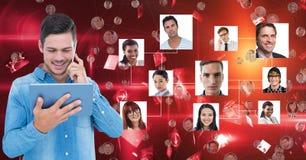 Homem novo pensativo que guarda a tabuleta digital ao estar contra retratos no fundo vermelho Imagens de Stock Royalty Free