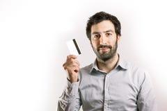 Homem novo positivo que guarda um cartão de crédito Imagens de Stock