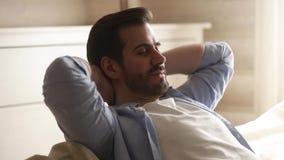 Homem novo preguiçoso feliz para relaxar a fantasia para meditar para sentar-se no sofá vídeos de arquivo