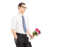 Homem novo preocupado com o laço que guarda um ramalhete das flores Imagens de Stock